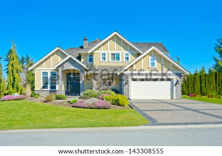 Big custom made luxury double garage doors house with nicely trimmed and landscaped front yard and paved driveway in the suburbs of Vancouver, Canada. - stock photo