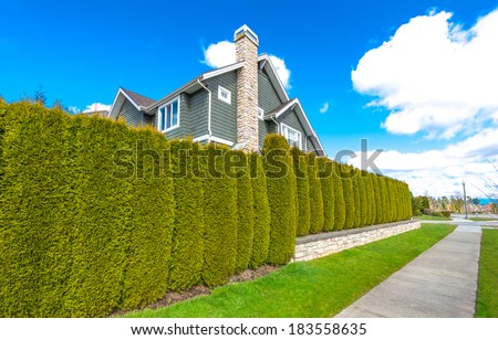Big custom made luxury house behind the green nicely trimmed fence in the suburbs of Vancouver, Canada. Keeps privacy and security. Landscape trimming design - stock photo