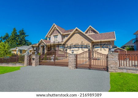 Big custom made luxury house behind the metal gates and nicely landscaped front yard and driveway to garage in the suburbs of Vancouver, Canada. - stock photo