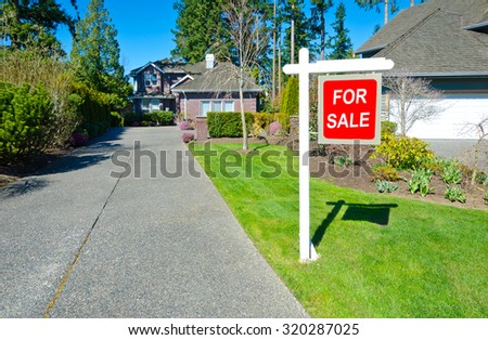 Big custom made luxury house for sale and with  nicely trimmed and landscaped front yard and long driveway in the suburbs of Vancouver, Canada.