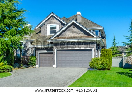 Big custom made luxury house, house entrance with nicely trimmed and landscaped front yard in the suburbs of Vancouver, Canada. - stock photo