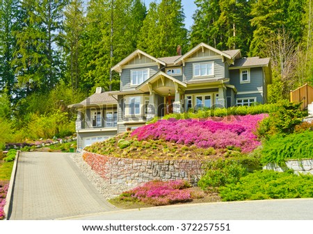 Big custom made luxury house on the rocky slope with nicely landscaped front yard and driveway to garage in the suburbs of Vancouver, Canada.