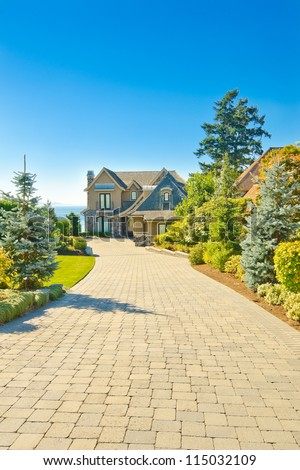 Big custom made luxury house with long nicely paved driveway in the suburbs of Vancouver, Canada. - stock photo