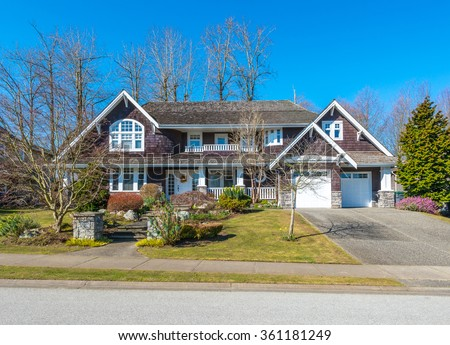 Big custom made luxury house with nicely landscaped and trimmed front yard and driveway to garage in the suburbs of Vancouver, Canada. - stock photo