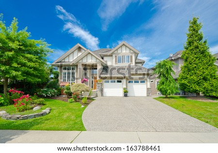 Big custom made luxury house with nicely landscaped and trimmed front yard and long driveway in the suburbs of Vancouver, Canada. - stock photo