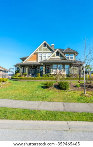 Big custom made luxury house with nicely landscaped and trimmed front yard in the suburbs of Vancouver, Canada. Vertical.