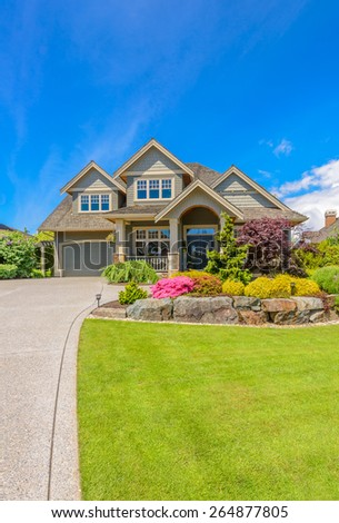 Big custom made luxury house with nicely landscaped front yard and driveway to garage in the suburb of Vancouver, Canada. Vertical. - stock photo
