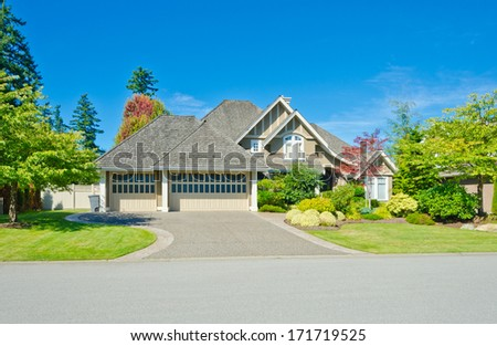 Big custom made luxury house with nicely landscaped front yard and long and wide driveway in the suburbs of Vancouver, Canada.