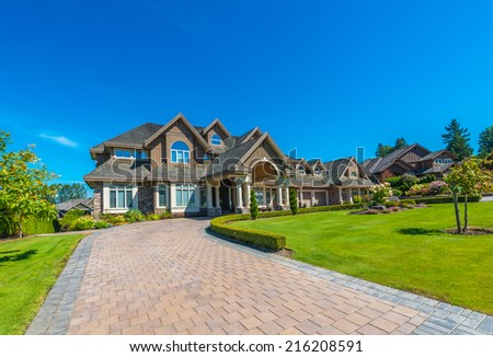 Big custom made luxury house with nicely landscaped front yard and paved driveway to garage in the suburbs of Vancouver, Canada. - stock photo