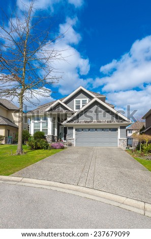 Big custom made luxury house with nicely landscaped front yard, double doors garage and long and wide driveway in the suburbs of Vancouver, Canada. Vertical. - stock photo