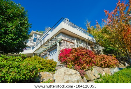 Big custom made luxury house with nicely landscaped front yard with some colorful bushes and rocks in the suburbs of Vancouver, Canada. - stock photo
