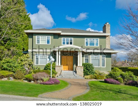 Big custom made luxury house with nicely paved long doorway and decorated and trimmed front yard in the suburbs of Vancouver, Canada.