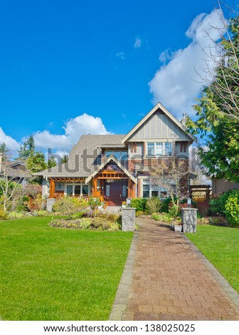Big custom made luxury house with nicely paved long doorway and trimmed front yard in the suburbs of Vancouver, Canada. Vertical.