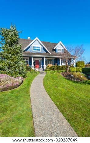 Big custom made luxury house with nicely trimmed and landscaped front yard and doorway in the suburbs of Vancouver, Canada. Vertical. - stock photo