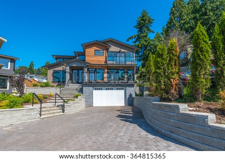 Big custom made luxury house with nicely trimmed and landscaped front yard and driveway to garage  in the suburb of Vancouver, Canada. - stock photo