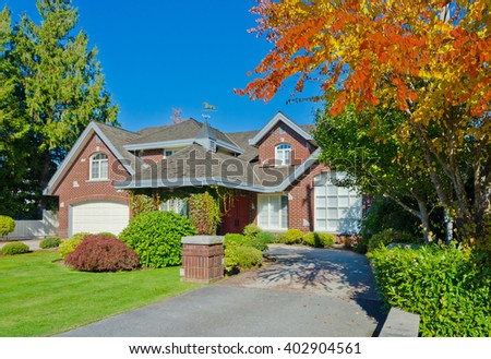Big custom made luxury house with nicely trimmed and landscaped front yard and driveway to garage in the suburbs of Vancouver, Canada.