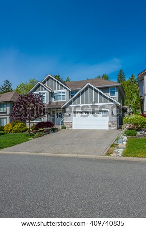 Big custom made luxury house with nicely trimmed and landscaped front yard and driveway to garage in the suburb of Vancouver, Canada.