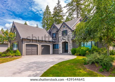 Big custom made luxury house with nicely trimmed and landscaped front yard and driveway to garage in the suburbs of Vancouver, Canada. - stock photo