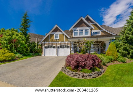 Big custom made luxury house with nicely trimmed and  landscaped front yard and driveway to the double doors garage in the suburb of Vancouver, Canada.