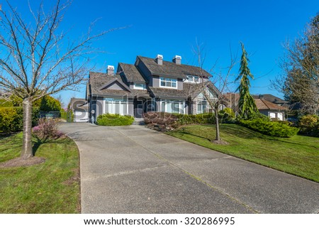 Big custom made luxury house with nicely trimmed and landscaped front yard and long driveway in the suburbs of Vancouver, Canada.