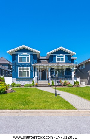 Big custom made luxury house with nicely trimmed and landscaped front yard  in the suburb of Vancouver, Canada. Vertical. - stock photo