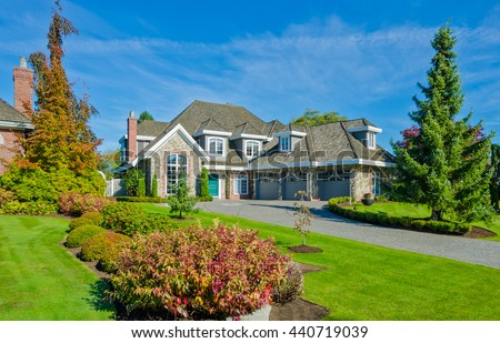 Big custom made luxury house with nicely trimmed and landscaped front yard in the suburbs of Vancouver, Canada. - stock photo