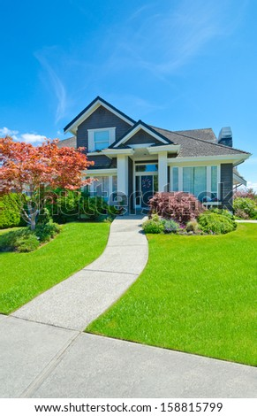 Big custom made luxury house with nicely trimmed and landscaped front yard lawn and long doorway in the suburbs of Vancouver, Canada. - stock photo