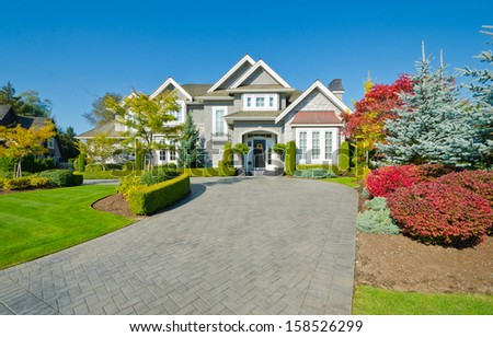 Big custom made luxury house with nicely trimmed and landscaped front yard lawn in the suburbs of Vancouver, Canada. - stock photo