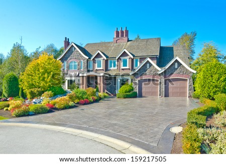 Big custom made luxury house with nicely trimmed and landscaped front yard, two doors garage and long and wide paved driveway in the suburbs of Vancouver, Canada. - stock photo
