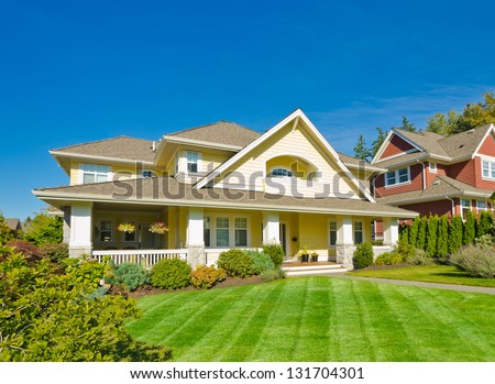 Big custom made luxury house with nicely trimmed front yard in the suburbs of Vancouver, Canada. - stock photo