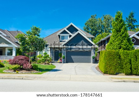 Big custom made luxury house with wide and long driveway and nicely  trimmed and landscaped front yard in the suburbs of Vancouver, Canada. - stock photo