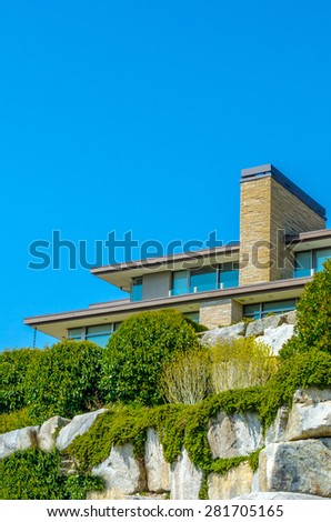 Big custom made luxury modern house on the rocks with nicely landscaped front yard in the suburbs of Vancouver, Canada. - stock photo