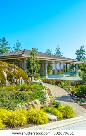 Big custom made luxury modern house with nicely landscaped front yard in the suburbs of Vancouver, Canada. Vertical. - stock photo