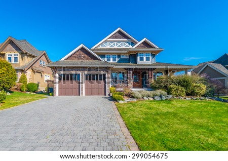 Big custom made luxury modern house with paved driveway and  nicely landscaped front yard in the suburbs of Vancouver, Canada. - stock photo