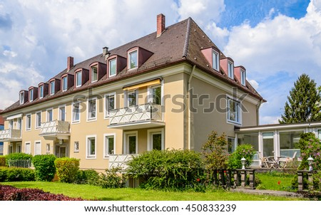Big custom made luxury three-storey house with a brown tile roof and green hedges - a typical austrian building in a residential neighborhood. A small gazebo with a tea table and a sun lounger - stock photo