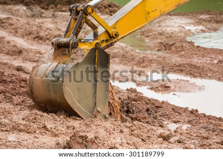 Big digger with brown mud on coastal lake - stock photo
