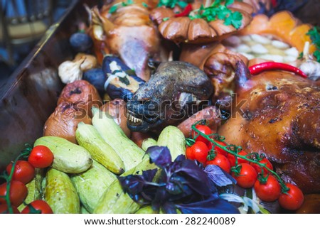 Big dish plate with roasted full pork head, served in restaurant with vegetables, lamb, ham and chicken. - stock photo