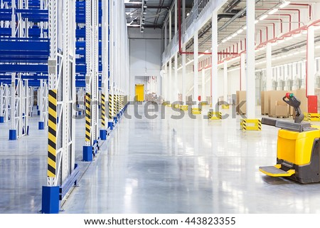 Big distribution warehouse with forklift for loading goods - stock photo