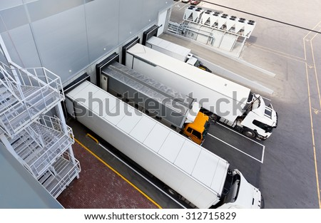 Big distribution warehouse with gates for loads and trucks - stock photo