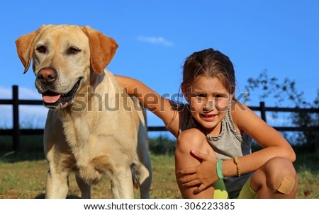 big Dog Labrador Retriever with lilttle girl in the park - stock photo