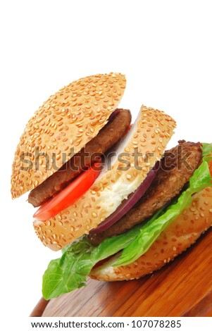 big double roasted hamburger on wooden plate with cutlery isolated  over white background - stock photo