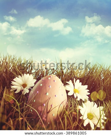 Big easter egg in the grass with daisies and blue sky