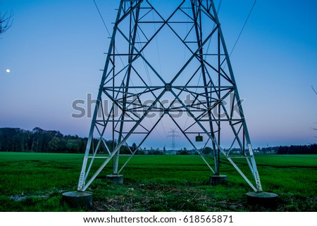 big electric power tower at sunset with a yellow moon in the background