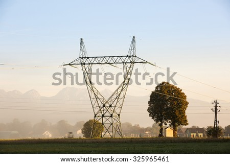 Big electricity high voltage pylon with power lines on a green grass in a misty morning near a village. Sustainable resources, green energy, energy and power industry concept.  - stock photo