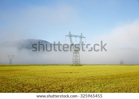Big electricity high voltage pylons with power lines on a yellow grass in a foggy morning. Sustainable resources, green energy, energy and power industry concept.  - stock photo