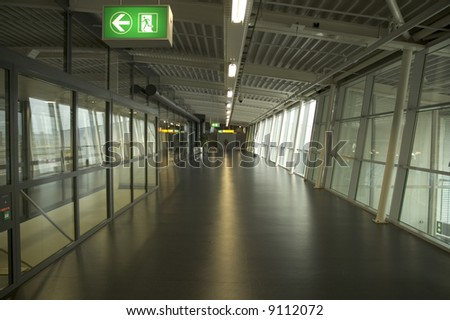 Big empty hall in airport with sign of emergency escape