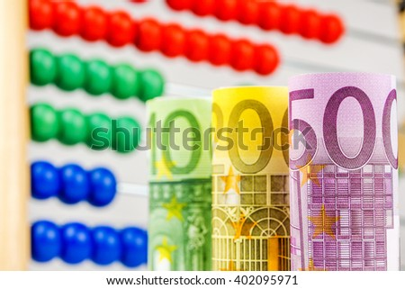 big euro banknotes with big wooden counter in the background as a school equipment and help for children, teaching them how to manage their finance in the future - stock photo