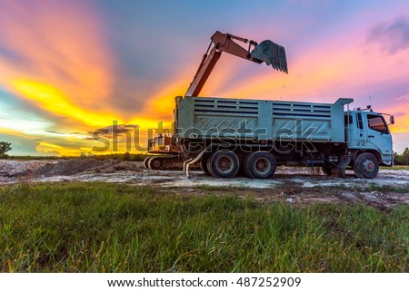 Big excavator transferring soil to the loading truck at twilight time