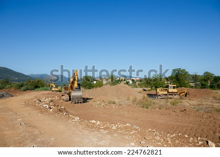 Big excavators on new construction site against a blue sky - stock photo