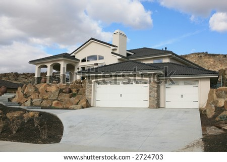 Big expensive modern house on a hill with puffy white clouds - stock photo